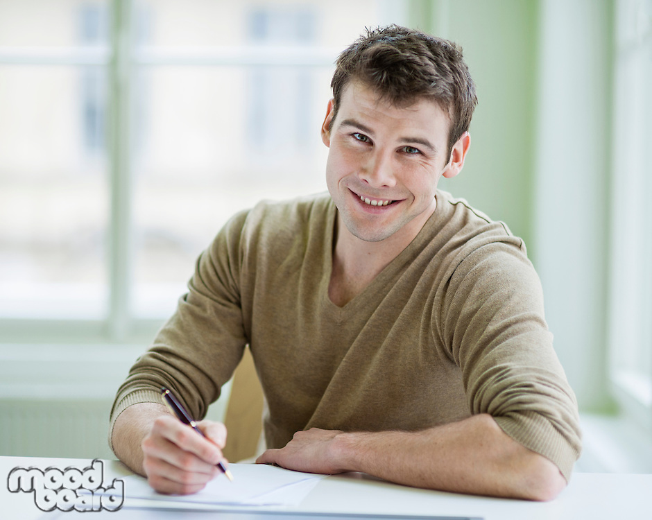 Portrait of handsome businessman writing on document at desk in office
