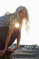 Young woman squatting on beach low angle view portrait