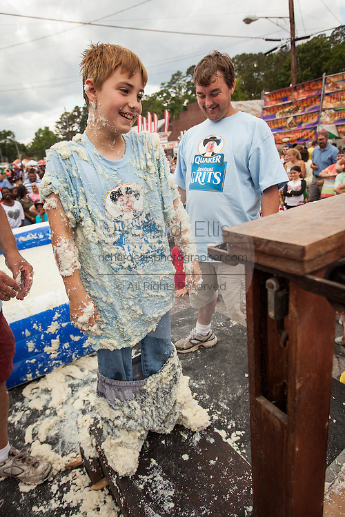 A competitor smiles as he is weighed after rolling in a pool of instant grits during the grits roll competition at the World Grits Festival April 14, 2012 in St. George, SC. The festival celebrates the southern love for the sticky corn porridge
