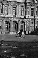 Person cycling past the water fountain at the Louvre, Paris, France<br />