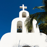 White church and palm tree in Playa del Carman, Mexico