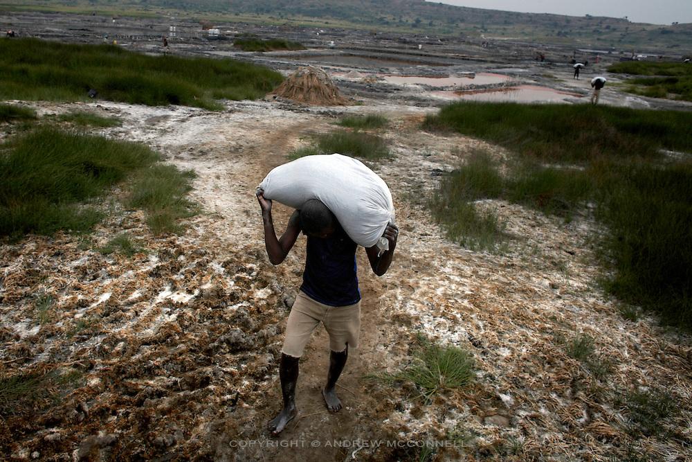 100 kg sacks of salt are carried to waiting trucks at Lake Katwe, Uganda.