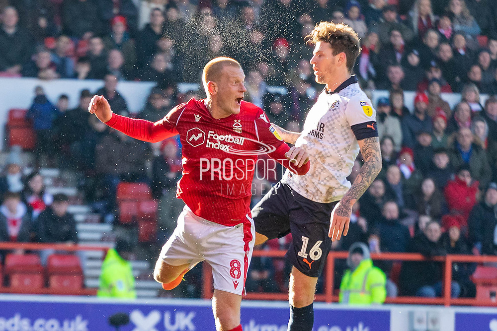 Ben Watson of Nottingham Forest clears ahead of Luton Town's Glen Rea (16) during the EFL Sky Bet Championship match between Nottingham Forest and Luton Town at the City Ground, Nottingham, England on 19 January 2020.
