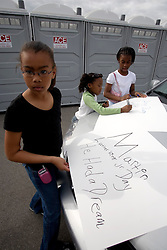 16 Jan, 2006. New Orleans, Louisiana. Post Katrina. Young girls made banners before a Martin Luther King Jr parade. The C3/Hands off Iberville coalition march almost 6 miles from the devastated Lower Ninth Ward to downtown New Orleans in an alternative protest to the Mayor's officially sanctioned celebrations marking Martin Luther King Jr day. The protest remembered those who perished and claims to stand up for the rights of displaced, primarily african americans.<br /> Photo; Charlie Varley/varleypix.com