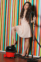 Portrait of young woman with vacuum cleaner standing against colorful striped wall