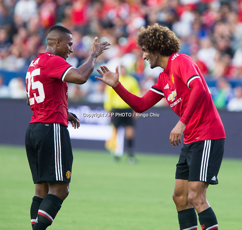 Manchester United Marouane Fellaini, left, celebrates his goal with teammate Antonio Valencia against Los Angeles Galaxy  during the first half of a national friendly soccer game at StubHub Center on July 15, 2017 in Carson, California.   AFP PHOTO / Ringo Chiu
