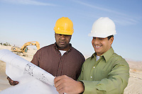 Two construction workers studying blueprint