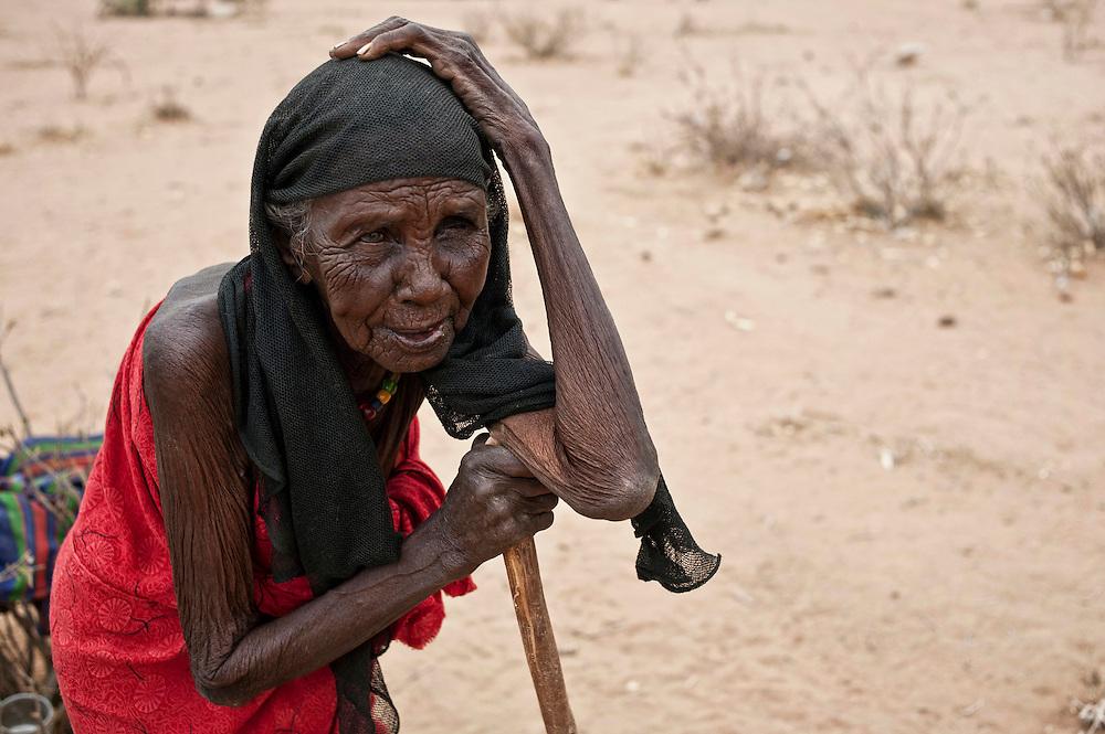 Kenya, camp de réfugiés de Dadaab - Ifo 3.                                                                             Halima, 80 ans selon l'estimation de ses enfants, de Salaghaley où elle vivait le long d'une rivière, elle a marché 25 jours accompagnée de sa communauté, environ 70 familles. Halima ne parle plus, ne possède plus qu'un oeil. Elle habite ici depuis deux mois, sous une tente précaire, construite par son fils et sa belle-fille, l'abri est fait de branchages, de tissus et de toiles qui lui ont été données lors de l'accueil au camp. Cette vieille dame  a choisi de se réfugier à Dadaab car ses animaux sont morts de faim durant la sécheresse qui sévit encore en Somalie. Elle laisse derrière elle son habitation, et les derniers animaux que possédaient sa communauté.  Certaines familles retourneront peut-être en Somalie pour retrouver leur ferme.