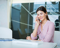 Beautiful young businesswoman using mobile phone at conference table