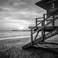San Clemente lifeguard tower three black and white photo with the sun setting over San Clemente Pier. Photo is high resolution. Copyright ⓒ 2017 Paul Velgos with All Rights Reserved.