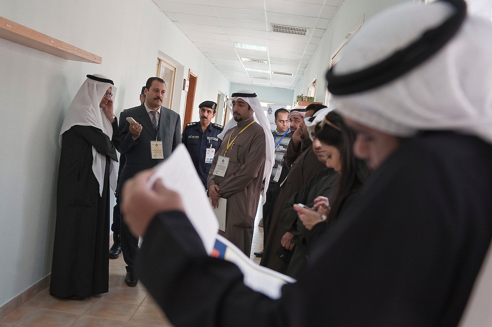 """Kuwaiti Justice, Education and Higher Education Minister Ahmad Al-Mulaifi talks on his mobile phone as he tours a polling station in Kuwait City during the Feb. 2 , 2012 parliamentary elections. The minister told reporters that he was confident that the voting process would run smoothly. """"Our democracy is an open book for all,"""" the minister was quoted as saying by local media.  A total of 400,296 Kuwaiti men and women are eligible to vote to choose from among some 285 candidates, including more than 20 women candidates, for a new 50-seat parliament."""
