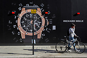 A man walks his bike past a construction hoarding of a watch outside the new Richard Mille shop in New Bond Street, on 25th February 2019, in London, England.