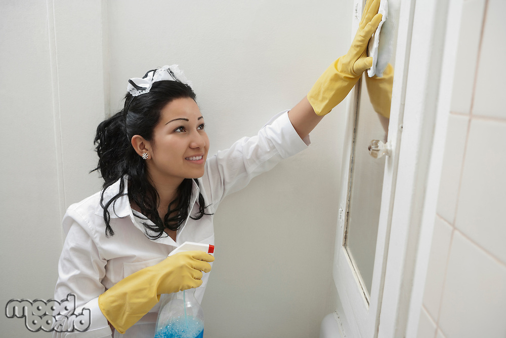 Young maidservant cleaning mirror