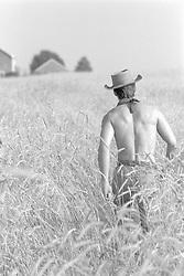 shirtless cowboy walking off through a field