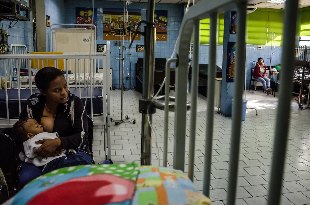 """CARACAS, VENEZUELA - JANUARY 21, 2015: Carmen Ramos, 39, (left) feeds her 1-year old son, Isoios Jaimez inside the pediatric ward of a state hospital in the Petare slum in Caracas.  Isoios is suffering from a respiratory infection, and Ms. Ramos has been unable to find the antibiotics prescribed to help him recover. She said her husband and her rotate shifts at the hospital taking care of their son, and waiting in lines at pharmacies in search of his medicines.  She said that doesn't leave them the time to wait in the long lines to find diapers, so they have to buy them on the blackmarket. She recently paid 350 bolivares, over $50 USD at the official rate, for one pack of diapers. """"I can't afford it, but I have to go out and buy [the diapers] wherever I can because he is a small baby,  I can't leave him without diapers"""". Despite being a petro-state with one of the largest oil reserves in the world, basic and advanced medical supplies from gauze and surgical gloves, to heart stints, are difficult to find in hospitals and pharmacies across Venezuela."""