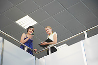 Two women looking over railing of indoor balcony