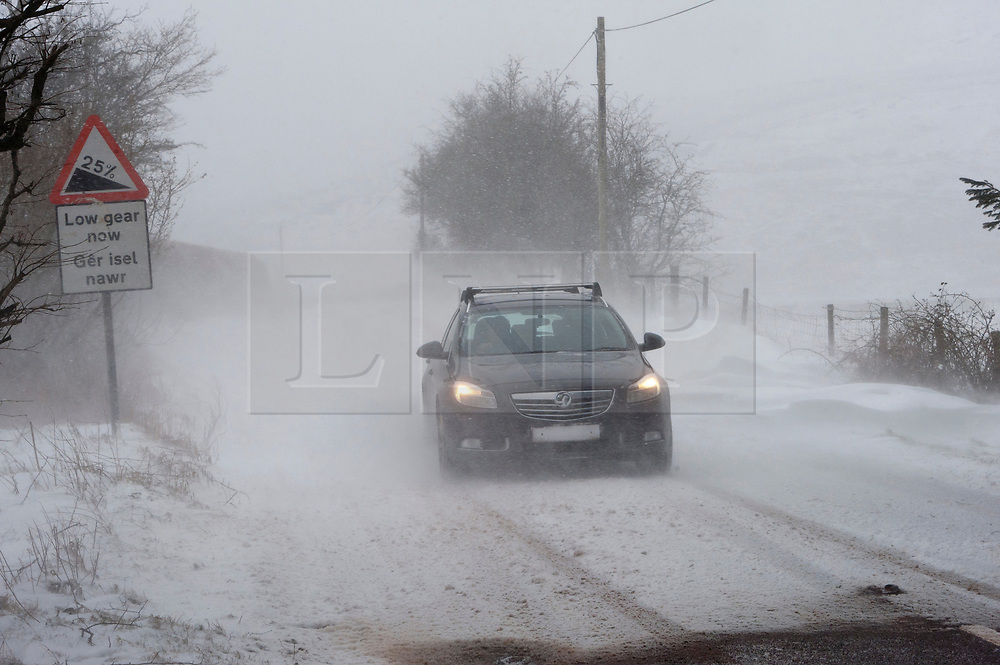 © Licensed to London News Pictures. 1/03/2018. Builth Wells, Powys, Wales, UK. On the first day of Spring, a motorist drives through horrendous blizzard conditions on the B4520 road (Brecon Road) between Builth Wells and Brecon on the high moorland of the Mynydd Epynt range. Blizzards and temperatures around minus 5-7 degrees Centigrade with 'feels like' of approximately minus 10 degrees on high land hit Mid Wales last night and today. Photo credit: Graham M. Lawrence/LNP