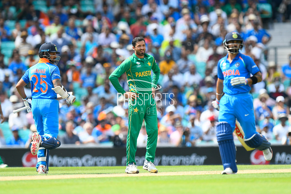 Junaid Khan of Pakistan with batsmen Shikhar Dhawan of India and Virat Kohli (captain) of India during the ICC Champions Trophy final match between Pakistan and India at the Oval, London, United Kingdom on 18 June 2017. Photo by Graham Hunt.