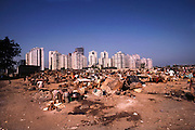 Slum with squatter's shelters near Nariman Point; high rise apartments in the background.  Bombay, India.
