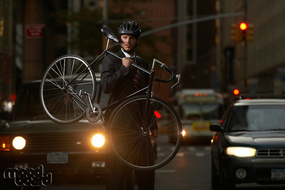 Man standing on street carrying bicycle portrait