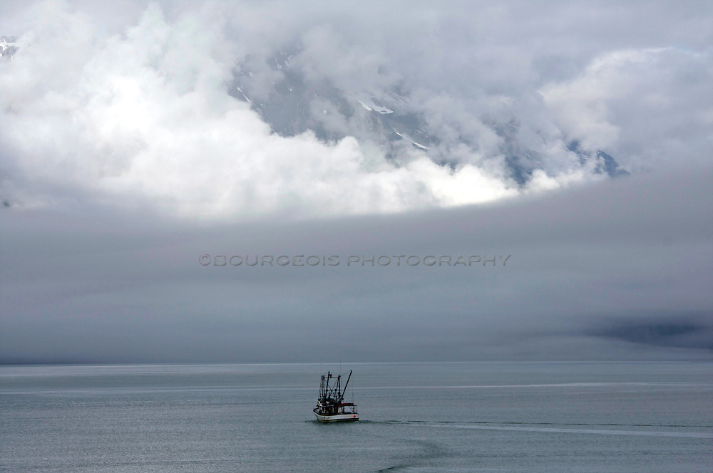 Southeast Alaska by boat. Sitka, Juneau, Ketchikan. Southeast Alaska fishing boat heads into heavy clouds and fog while a glacier sits and retreats.