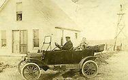 Man and woman in early automobile posing for photo on the homestead.