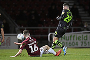 Northampton Town defender (on loan from Blackburn Rovers) Scott Wharton (16) slides in to tackle Forest Green Rovers forward (on loan from Celtic) Jack Aitchison (29) during the EFL Sky Bet League 2 match between Northampton Town and Forest Green Rovers at the PTS Academy Stadium, Northampton, England on 14 December 2019.