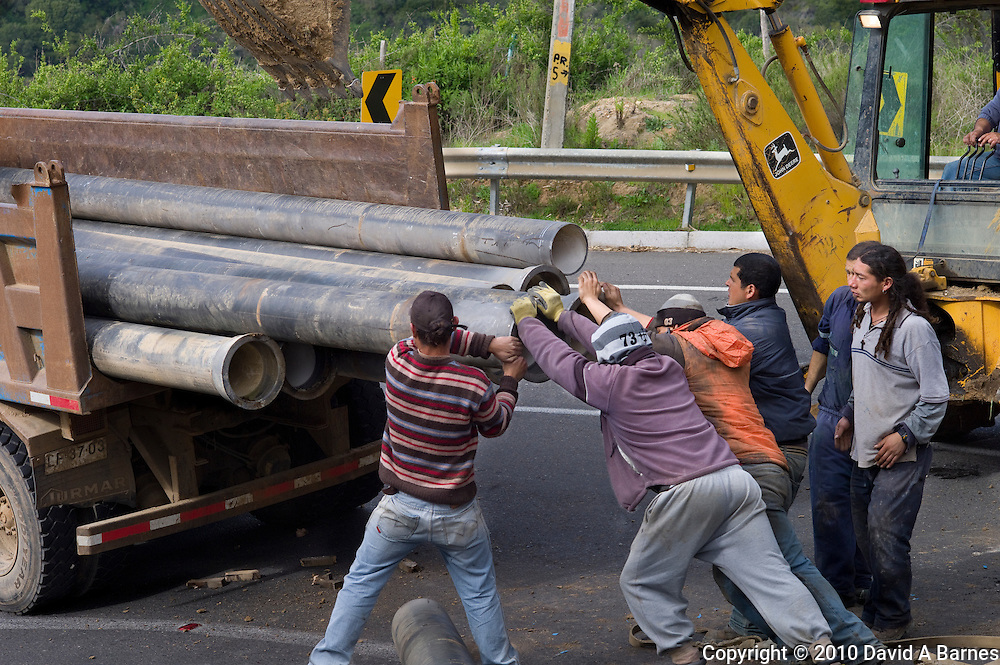 Men putting pipes back in truck after they fell out, Chile