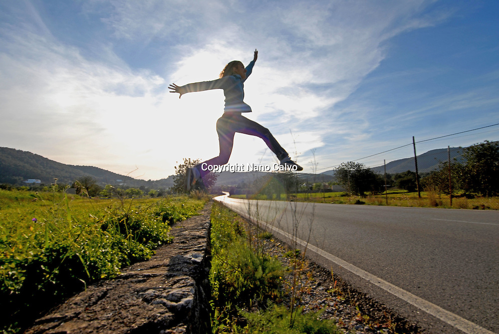 MR Young woman jumping on the road, in a beautiful sunset, Ibiza, Spain