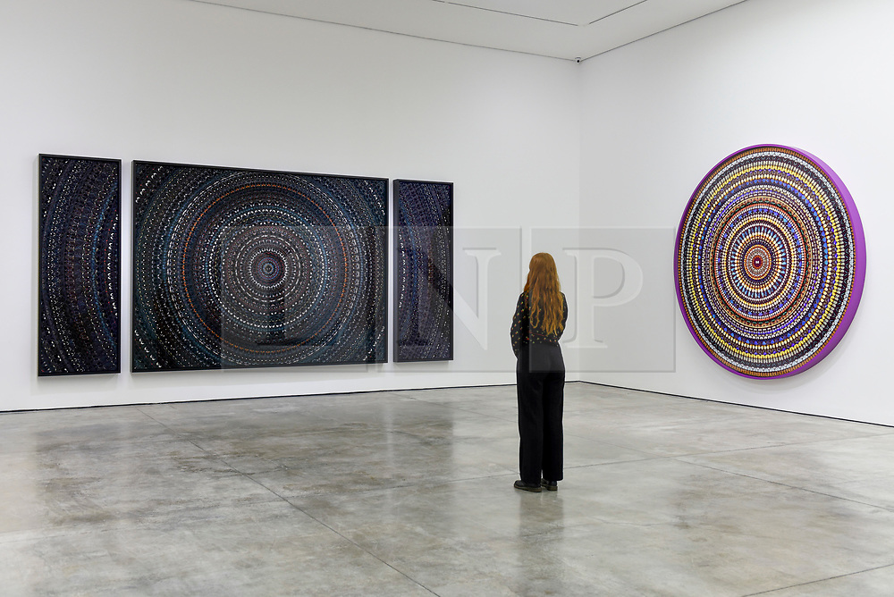 "Licensed to London News Pictures. 19/09/2019. LONDON, UK.  A staff member poses between (L to R) ""The Creator"" 2019, and ""Radial Balance"", 2019, both by Damien Hirst.  Preview of a new exhibition by Damien Hirst at White Cube's Mason's Yard gallery in Mayfair.  It is the artists first major solo exhibition in seven years and features large-scale concentric butterfly paintings from his new ""Mandalas"" series.  22 large scale works are on display 20 September to 2 November 2019..  Photo credit: Stephen Chung/LNP"