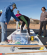 Air marking with Phoenix 99s at Eagle Nest in Aguila, AZ on February 10, 2018.<br /> <br /> Phyllis Wells, left, bundled up against the cold wind, sorts out the equipment for Judy Yerian (behind Phyllis's arm), Courtney Smith and Felecia Zahn, far right.