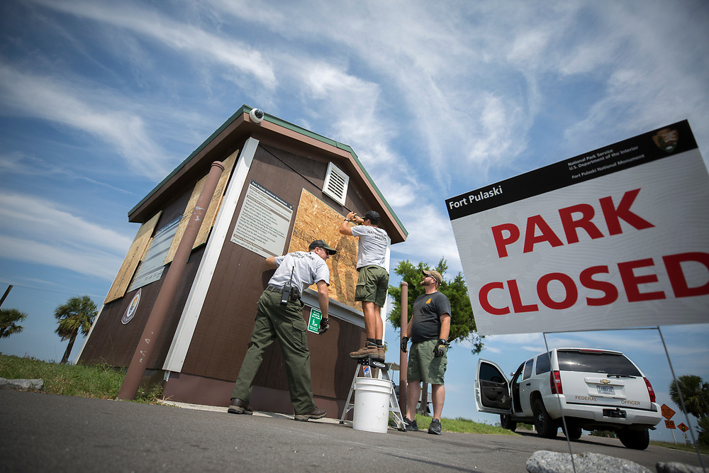 National Park Service employees Joel Cadoff and Miguel Rome board up the entrance station, Friday, Sept., 8, 2017, before Hurricane Irma hits the area near Tybee Island, Ga.  (Stephen B. Morton for The Atlanta Journal Constitution)