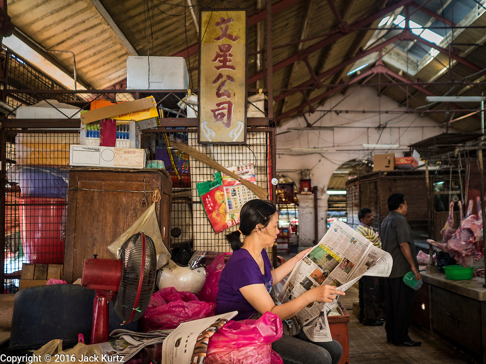 17 NOVEMBER 2016 - GEORGE TOWN, PENANG, MALAYSIA:  A vendor reads a newspaper while she waits for customers in the Campbell Street Market in George Town, Penang, Malaysia. George Town is a UNESCO World Heritage city and wrestles with maintaining its traditional lifestyle and mass tourism. The market is not very busy anymore.       PHOTO BY JACK KURTZ