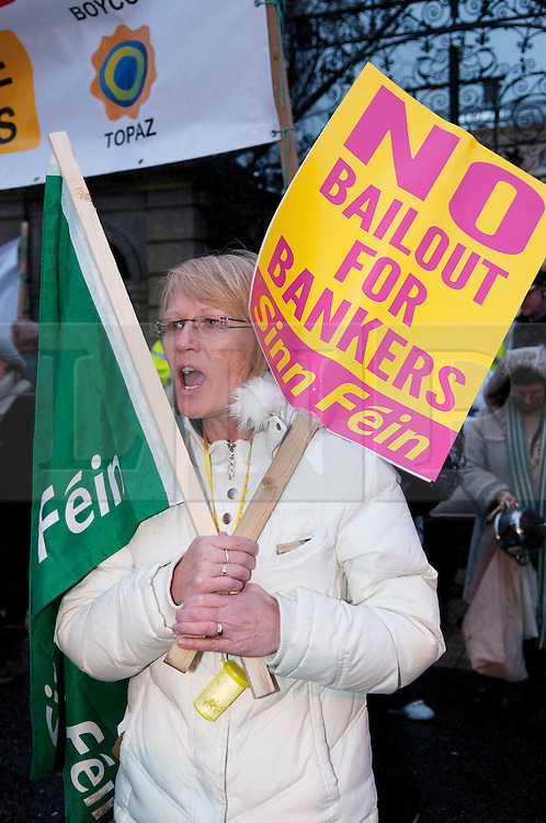 © under license to London News Pictures.  07/12/2010. A woman joins the crowd outside Leinster House in Dublin, Ireland, as they demand the IMF to withdraw their proposted bailout on 7/12/2010. Photo credit should read Michael Graae/London News Pictures