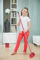 Portrait of a young girl sweeping floor with broom