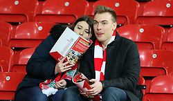Liverpool fans in the stands read the programme
