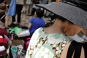 woman with hat at a outdoors secondhand clothing market
