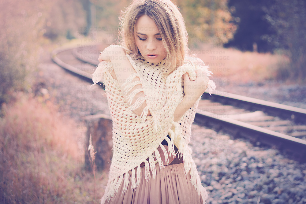 A beautiful  young woman with blonde hair standing outside at a train track wearing a long skirt and a crochet stole