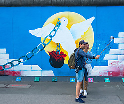 Tourist taking selfie,photograph of mural painted on original section of Berlin Wall at East Side gallery in Berlin, Germany ...Editorial Use Only