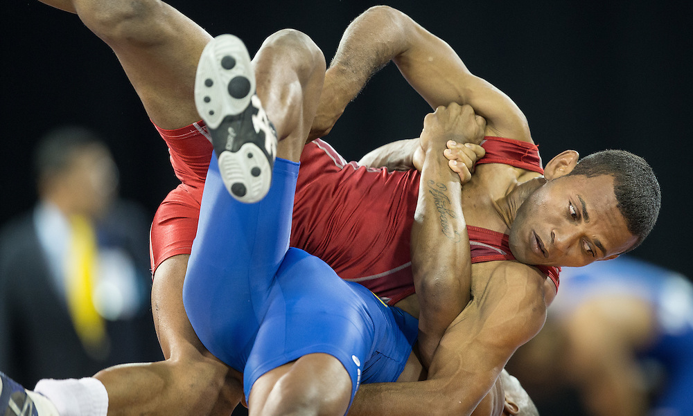 Jansel Ramirez of the Dominican Republic is thrown by Andres Montano of Ecuador during their quarter final bout in the 59kg class of the men's greco-roman wrestling  at the 2015 Pan American Games in Toronto, Canada, July 15,  2015.  AFP PHOTO/GEOFF ROBINS