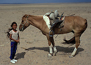 Mongolia, Gobi desert. July 1996: Munkhtsetseg's sister poses with her horse in the Gobi desert.