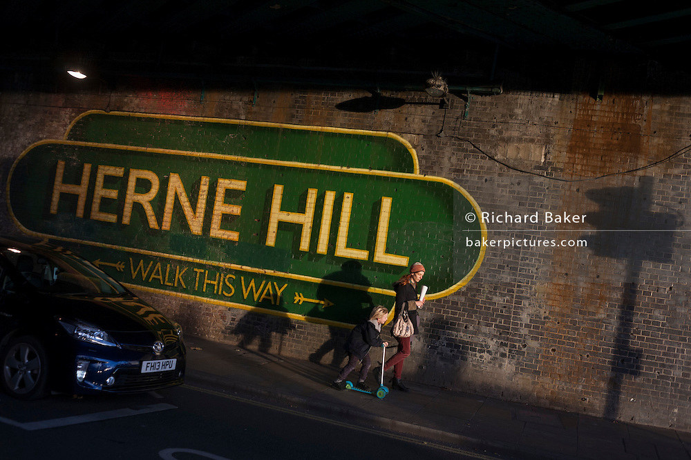 Pedestrians walk beneath the large sign under the railway bridge announcing Herne Hill, Lambeth SE24 south London. The mural is one of many in south London by the artist Lionel Stanhope.