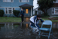 (Gabe Green | The Daily World)<br /> <br /> Humberto Morales Games, 11, uses two folding chairs to navigate across a flooded H Street in Aberdeen while playing with Jonah Showalter, 13, out side of their house Monday afternoon.