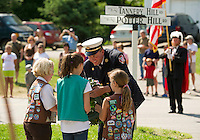 "Gilford Fire Chief Stephen Carrier assists the Girl Scouts for the ""placing of the wreath"" on the World War I & II memorial at the start of the Memorial Day parade Monday morning.  (Karen Bobotas/for the Laconia Daily Sun)"