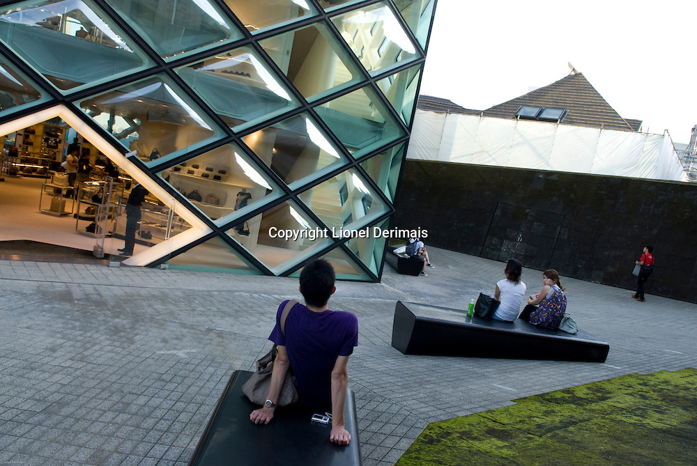 Passers-by take a rest in front of the .Prada store in Aoyama, Tokyo designed by Herzog&DeMeuron.