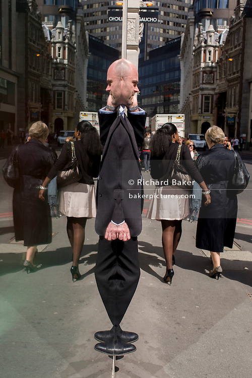 As two women walk away, a City businessman makes a call while reflected in a plate glass window.
