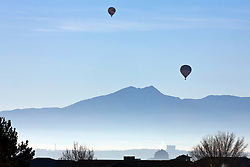 Two hot air balloons at sunrise with Sandia mountains in the background, Albuquerque, New Mexico, United States of America