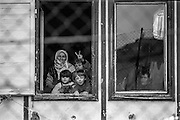 "Refugees from Bosnia in the Varazdin refugee camp in Croatia in the winter of 1992. The woman on the left is grandmother ""Nana"" with her nephew ""Elvis"" (second on the left, first line) and his sister Elvira beside him looking out of the  window of a barrack where they lived as refugees."
