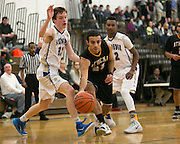 Zac DiSalvo of Greece Athena squeezes between two defenders during a game at Webster Schroeder High School on Friday, January 23, 2015.