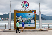 "People walking on Odongdo island in Yeosu which is connected to the shore by a 768-meter-long breakwater. Yeosu will host the Expo 2012 exhibition  under the theme ""The Living Ocean and Coast"". Yeosu (Yeosu-si) is a city in South Jeolla Province. Old Yeosu City, which was founded in 1949, Yeocheon City, founded in 1986, and Yeocheon County were merged into a new city in 1998."